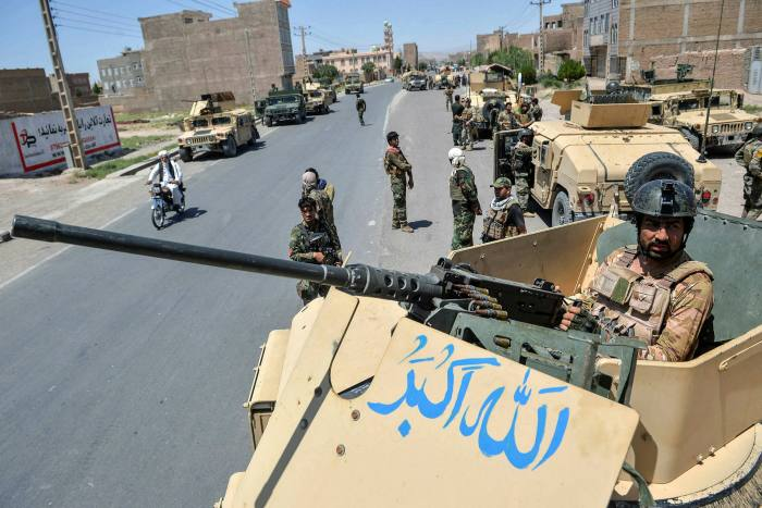 An Afghan army commando stands guard from a vehicle in Herat province