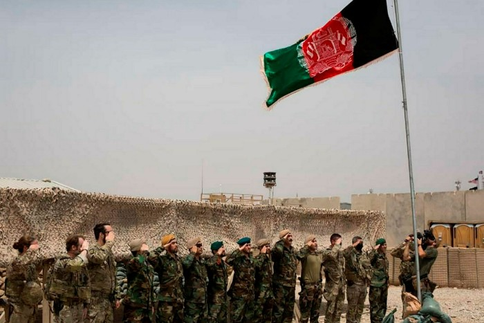 An Afghan flag flies as US and Afghan soldiers salute during a handover ceremony at Camp Anthonic in Helmand Province