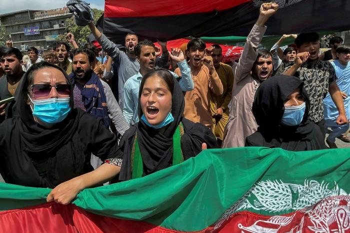 People carry the national flag during a protest held on August 19 during Afghan Independence Day in Kabul